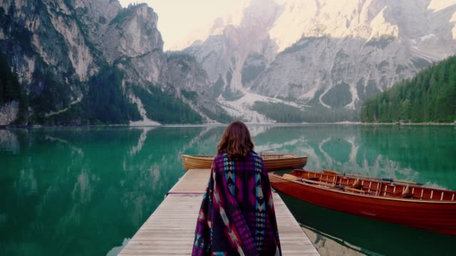 dolomites lago di braies gölü yakınlarında yürüyen kadın - turistik yer stok videoları ve detay görüntü çekimi