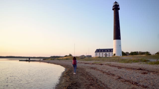 Woman walking near the lighthouse on the beach at sunset