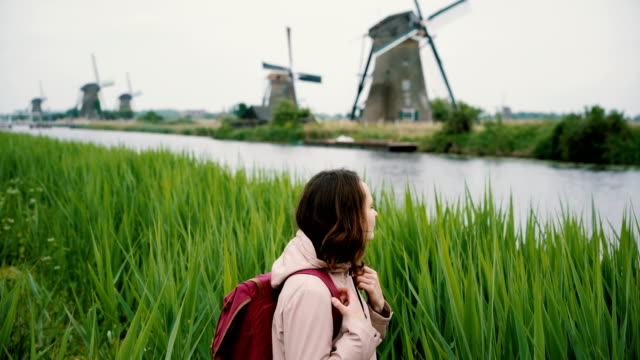 Woman walking near windmills in the Netherlands