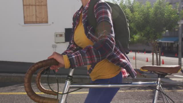 Woman walking next to her bike with medical coronavirus mask on the street