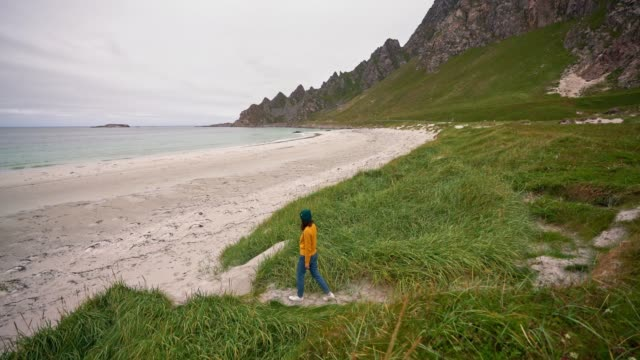 Woman walking  on a beach on Lofoten island