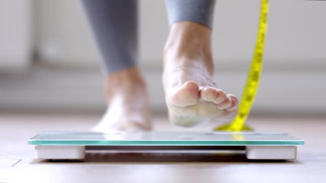 Woman walking on a body weighing scale