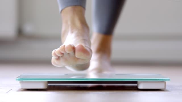 kvinna som går på en kropps vägning skala - byxor bildbanksvideor och videomaterial från bakom kulisserna