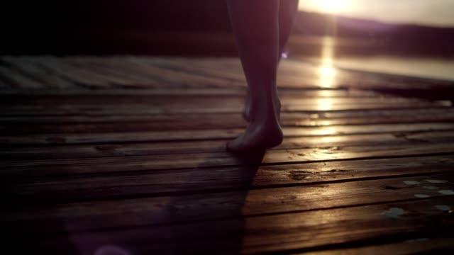 bir göl iskelede yürüyen kadın. göl günbatımı - dalgakıran stok videoları ve detay görüntü çekimi