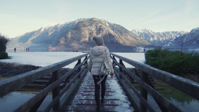 vídeos de stock, filmes e b-roll de mulher que anda em um pontão no lago hallstatt - áustria
