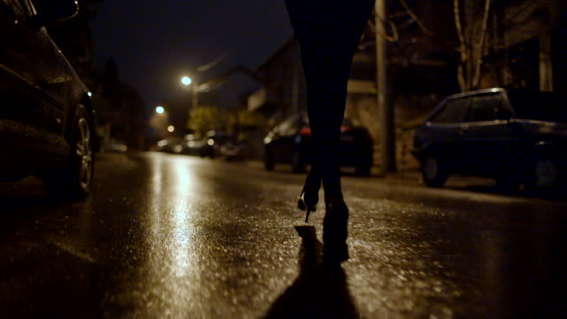 Woman walking on a street at night Low angle view point of female legs walking in the dark.  alley stock videos & royalty-free footage