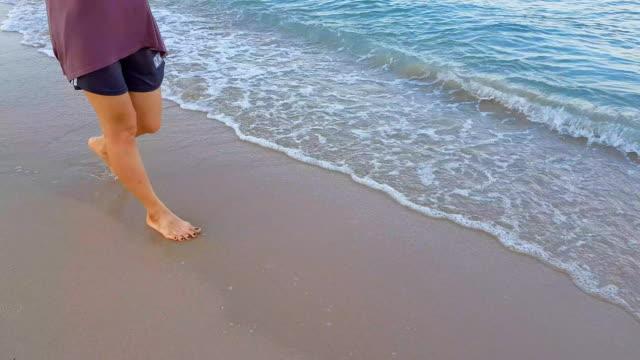 Woman walking on beach Woman jogging along the beach water splash grace bay stock videos & royalty-free footage