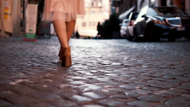Woman walking on cobblestone pavement road. Girl exploring new city wearing in shoes and skirt. Close-up view