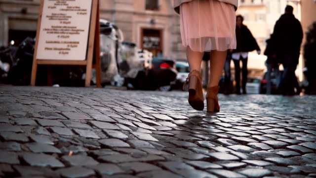 Woman walking on cobblestone pavement road in city. Girl exploring town wearing in high shoes and skirt. Close-up view video