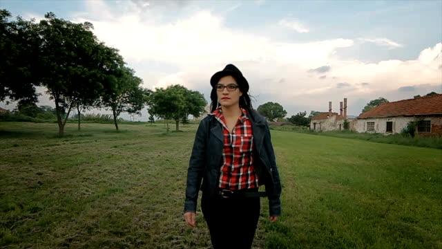 donna che cammina sul campo,ripresa di stabilizzazione della telecamera - potere femminile video stock e b–roll