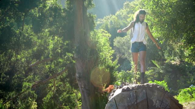 Woman walking on log in park video