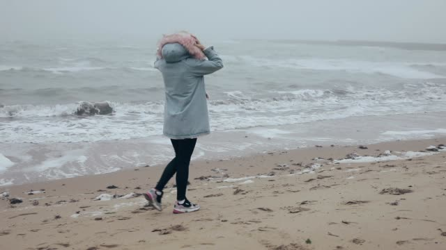 Woman walking on ocean coast enjoying freedom of nature video