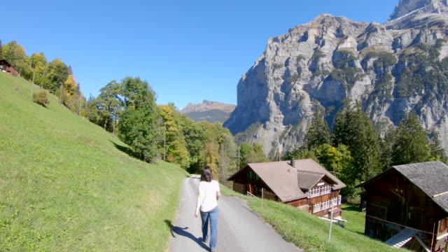 woman walking on paved road in alpine landscape - время дня стоковые видео и кадры b-roll