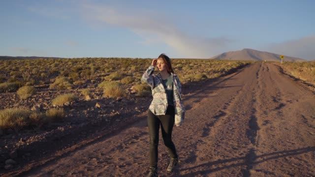 Woman walking on road in Atacama desert in Chile