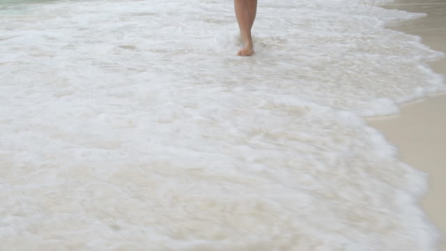 Woman walking on sandy beach on beautiful day. Slow motion video