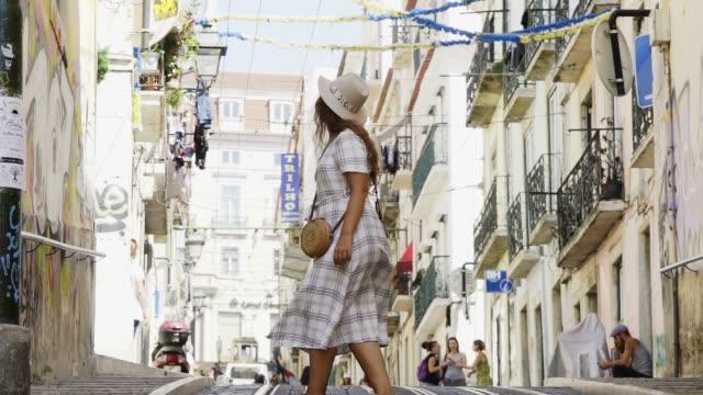 vídeos de stock e filmes b-roll de woman walking on street between old buildings - eletrico lisboa