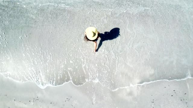 woman walking on the beach - drone view