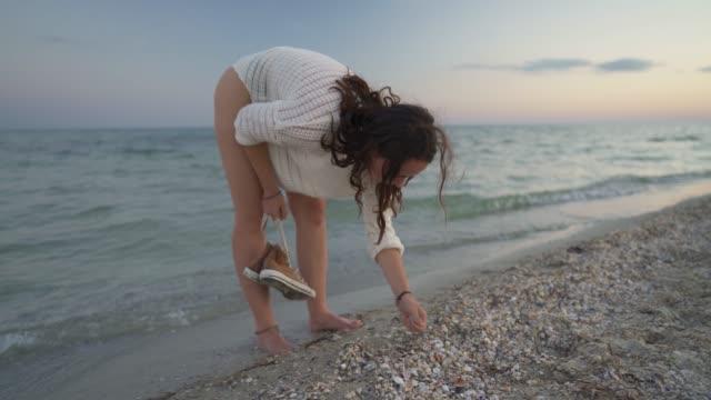 vidéos et rushes de femme marchant sur la plage - coquille et coquillage