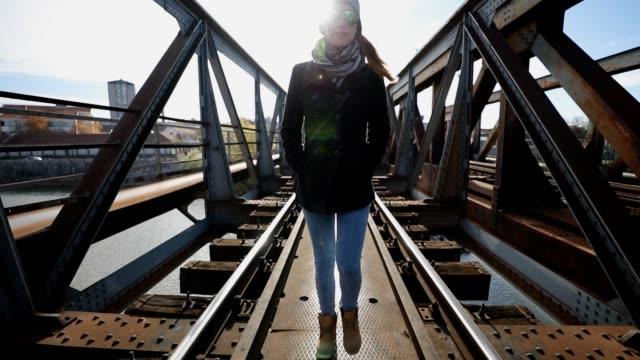 stockvideo's en b-roll-footage met vrouw lopen op de brug - street style