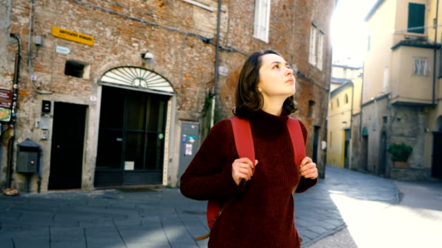 Woman walking on the streets of Lucca, Italy Young Caucasian woman walking on the streets of Lucca, Italy renaissance architecture stock videos & royalty-free footage