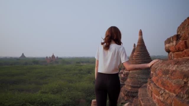 ストゥパの上を歩き、バガン遺産の美しい景色を眺める女性 - 仏塔点の映像素材/bロール