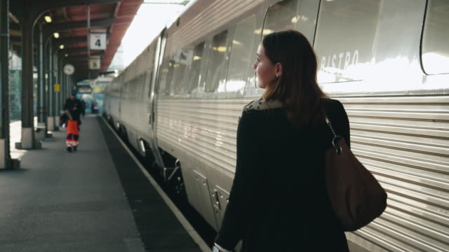 woman walking on train station platform - train stock videos and b-roll footage