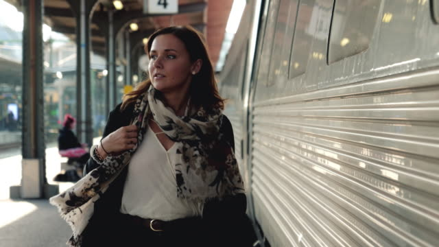 Woman walking on Train Station Platform A beautiful young woman walking down the platform and waiting for the train at the station. Shot in 4K resolution. station stock videos & royalty-free footage