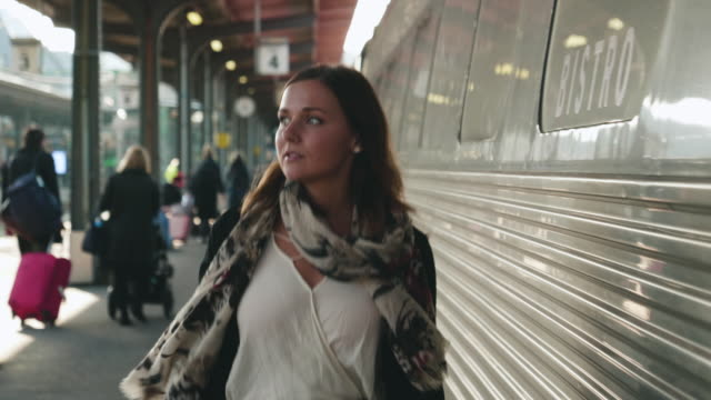 Woman walking on Train Station Platform A beautiful young woman walking down the platform and waiting for the train at the station. Shot in 4K resolution. railroad station platform stock videos & royalty-free footage