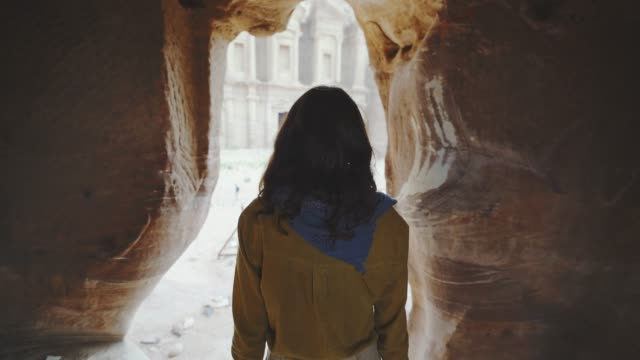 woman walking out of  siq canyon and looking at treasury in petra - esploratore video stock e b–roll