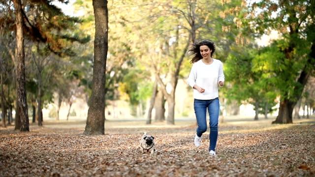 Woman walking pug in a park