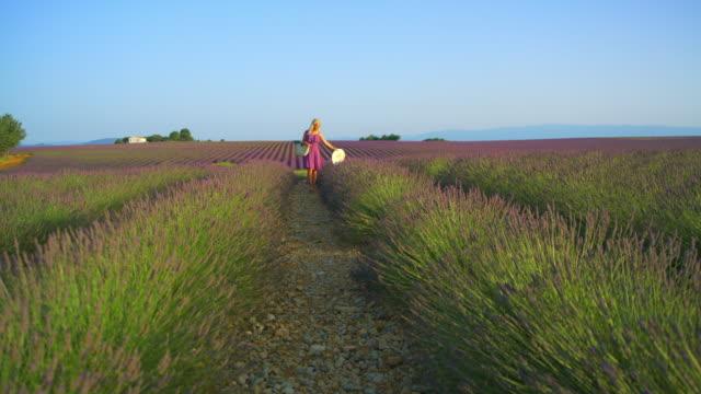 WS Woman walking through a field of lavender