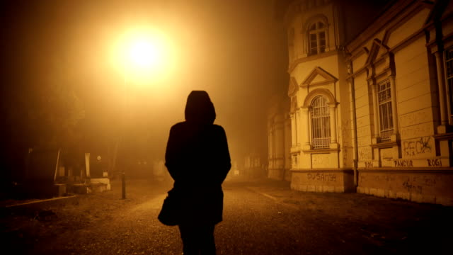 woman walking through a misty night