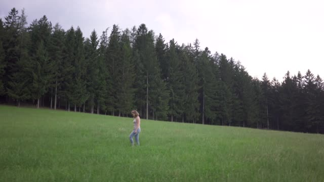 kvinna går genom gräsplan mot skog - människorygg bildbanksvideor och videomaterial från bakom kulisserna