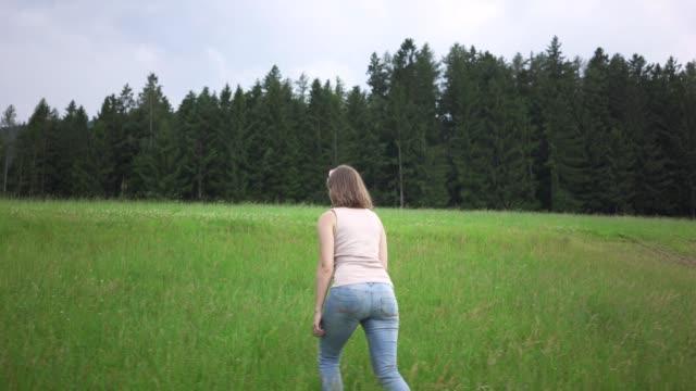 kvinna går genom gräsplan i skogen mot dramatisk himmel - människorygg bildbanksvideor och videomaterial från bakom kulisserna