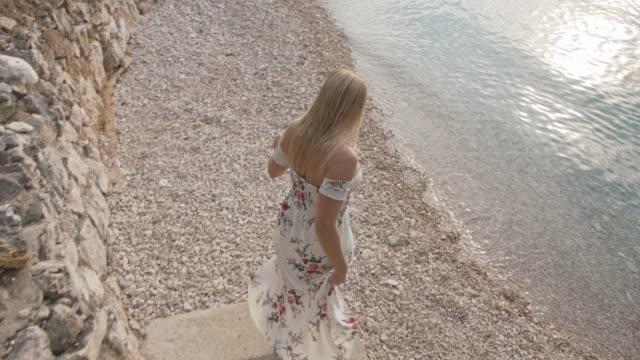 stockvideo's en b-roll-footage met de vrouw die van ts aan een strand loopt - mid volwassen vrouw