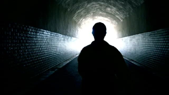 Woman walking to light in dark tunnel