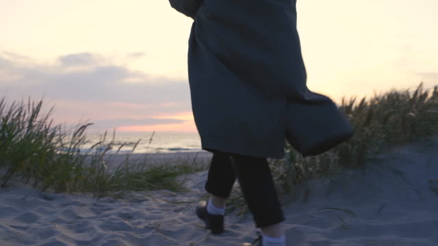 Woman walking to the beach at sunset