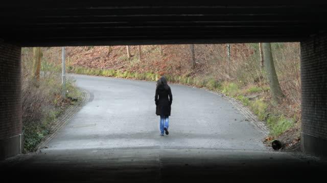 Woman walking under a bridge in 4K. Lonely melancholic sad atmosphere concept of destiny journey road direction