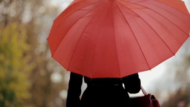 Woman walking under red umbrella, slow motion video