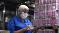istock Woman walking using digital tablet wearing face mask - working at warehouse / industry 1218037417