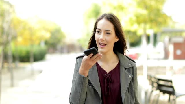 vídeos de stock, filmes e b-roll de mulher andar usando o reconhecimento de voz no telefone em um parque - discurso
