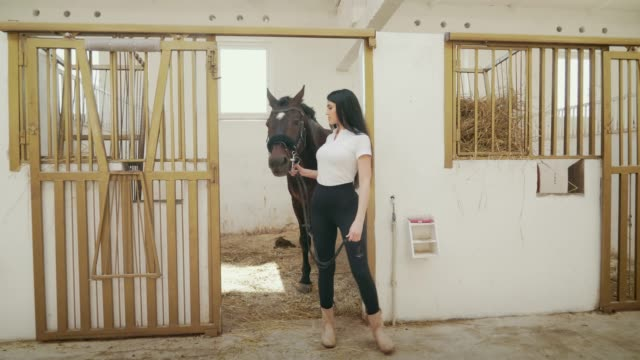 Woman walking with horse out of stable.