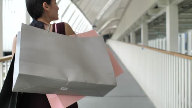 woman walking with shopping bag walking on the street - femminilità video stock e b–roll