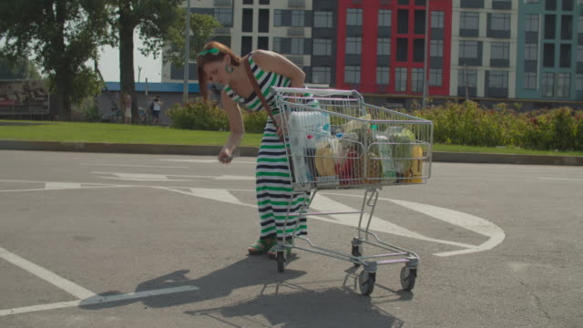 Woman walking with shopping cart and talking by mobile phone and accidentally dropping her mobile phone. Cell phone smashes on the ground. Lady with broken smart phone on car parking. Woman walking with shopping cart and talking by mobile phone and accidentally dropping her mobile phone. Cell phone smashes on the ground. Lady with broken smart phone on car parking. 4k footage woman pushing cart stock videos & royalty-free footage