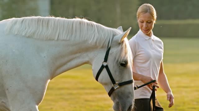 SLO Missouri TS Femme marchant avec cheval blanc dans la nature - Vidéo