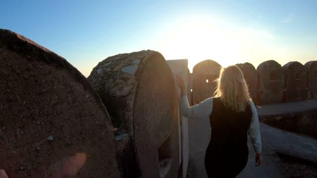 女性は日の出、古代の砦の壁に沿って歩く - 石垣点の映像素材/bロール