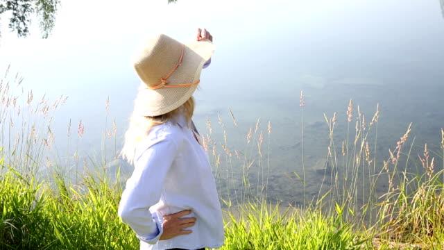Woman walks along edge of mountain pond video