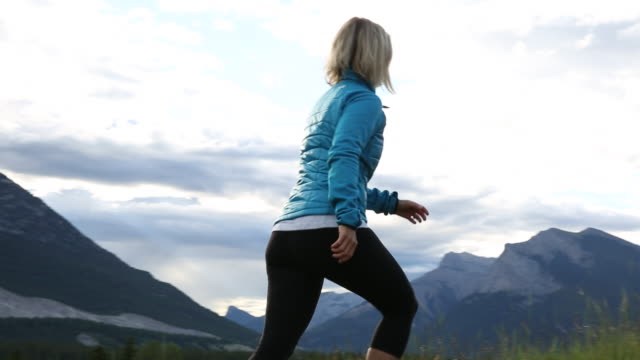 Woman walks along grassy ridge crest, in mountains  pedal pushers stock videos & royalty-free footage
