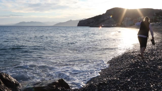 woman walks along pebble beach at sunrise - pantaloni capri video stock e b–roll