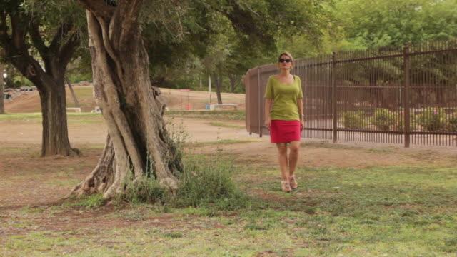 donna cammina per alberi - colore saturo video stock e b–roll